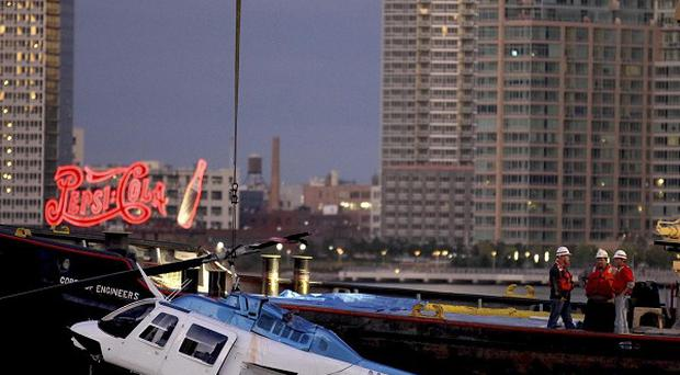 A helicopter that crashed into the East River in New York is hoisted from the water (AP)