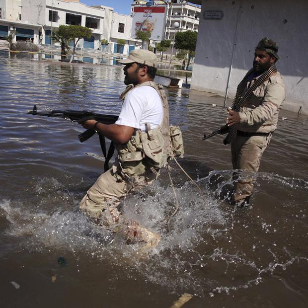 Revolutionary fighters run to take cover in Sirte, Libya (AP)