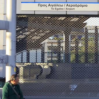 A commuter sits outside at a closed metro station during a 48-hour strike by public transport workers in Athens (AP Photos)