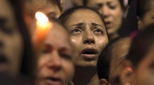 Egyptian Christians light candles to mourn victims of clashes with security forces in central Cairo (AP)