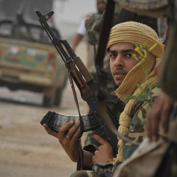 A Libyan revolutionary fighter rests as rebel forces try to secure an area controlled by pro-Gaddafi forces in Sirte (AP)