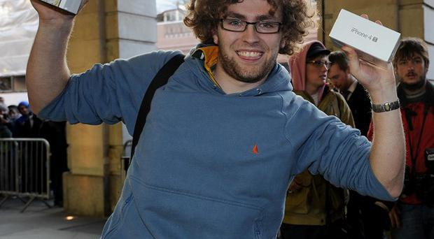 Mathew Kelly, 19, from Swansea, shows off his new iPhone 4S outside the Apple store in Covent Garden, London