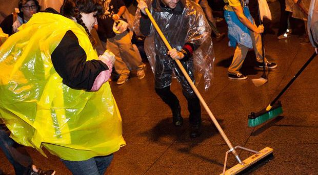 In a last-ditch bid to stay, protesters mopped and picked up rubbish at the site of an Occupy Wall Street demo (AP)
