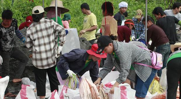 Villagers join forces to make sand bags for flooding barriers in Pathum Thani province, central Thailand (AP)
