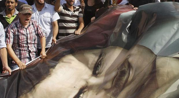 Syrian regime supporters wave a large portrait during a demonstration to show their support for President Bashar Assad (AP)