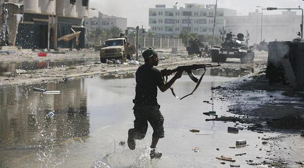 A Libyan revolutionary fighter fires with his machine-gun while attacking pro-Gaddafi forces in Sirte (AP)