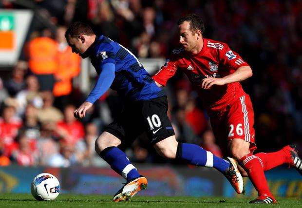 LIVERPOOL, ENGLAND - OCTOBER 15: Wayne Rooney of Manchester United competes with Charlie Adam of Liverpool during the Barclays Premier League match between Liverpool and Manchester United at Anfield on October 15, 2011 in Liverpool, England. (Photo by Clive Brunskill/Getty Images)