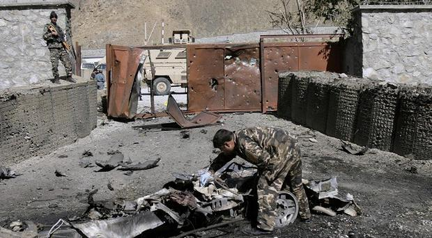 A security officer collects evidence from the site of an attack by militants at the gate of an American base in Panjshir, north of Kabul, Afghanistan (AP)