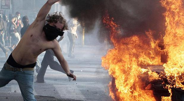 A masked protestor hurls a cannister during clashes in Rome (AP)