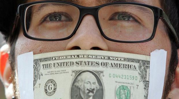 Franko Lucarelli covered his mouth by a dollar bill as thousands of protesters marched through the financial district in Los Angeles (AP)