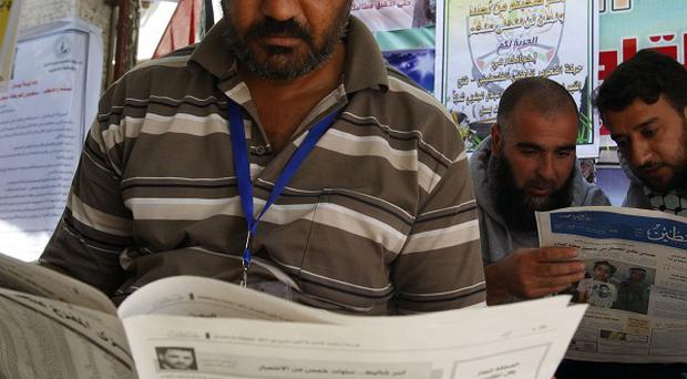 Palestinians look at the lists of prisoners who are to be exchanged for captured Israeli soldier Gilad Schalit (AP)