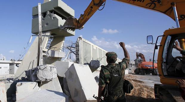 Revolutionary fighters use heavy machinery to tear down a guard tower at Muammar Gaddafi's compound in Tripoli (AP)