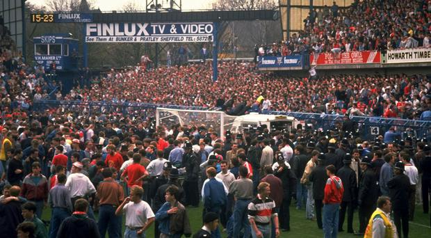 Liverpool fans spill on to the pitch during the crush in the Leppings Lane end at Hillsborough at the 1989 FA Cup semi-final; 96 lost their lives