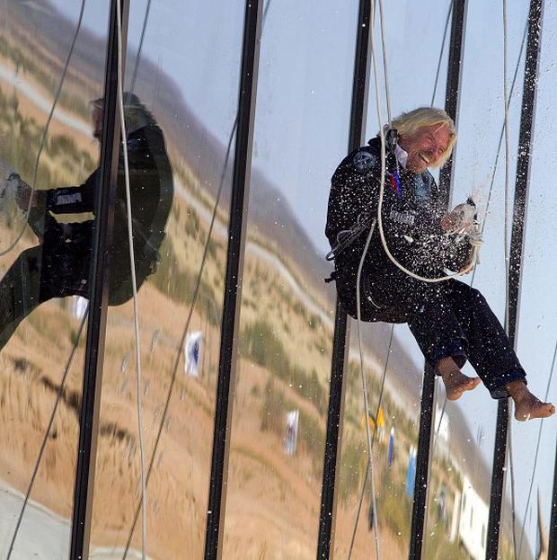 Sir Richard Branson sprays champagne after abseiling down the side of the new spaceport for his Virgin Galactic space tourism venture (AP)