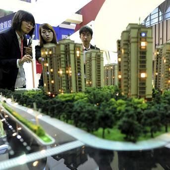 Sales promoters talk to visitors at a housing fair in Nanjing (AP)