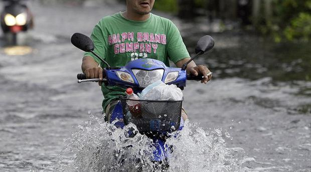 Motorcyclists make their way through a flooded street in Nonthaburi province, north of Bangkok(AP)