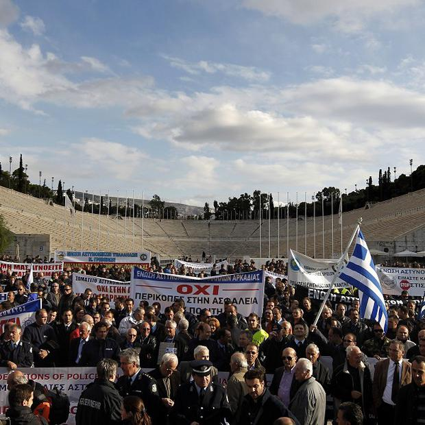 Police officers, firefighters and coastguard officers take part in a protest at the Panathenaean Stadium in Athens (AP)