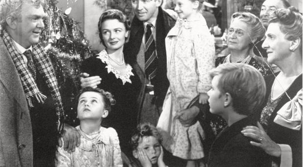 In this 1946 file photo, legendary actor James Stewart as George Bailey, center, is reunited with his wife played by actress Donna Reed, third from left, and family during the last scene of Frank Capra's