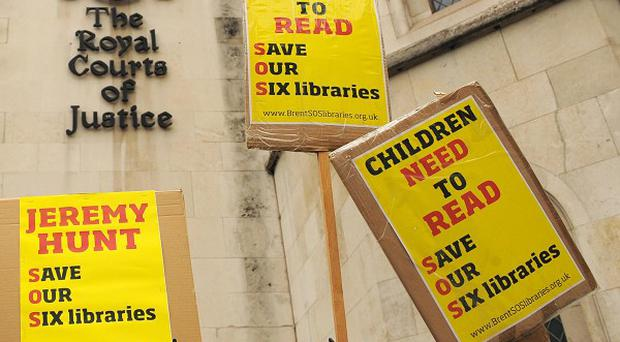 Save Our Six Libraries signs outside the Royal Courts of Justice, in central London