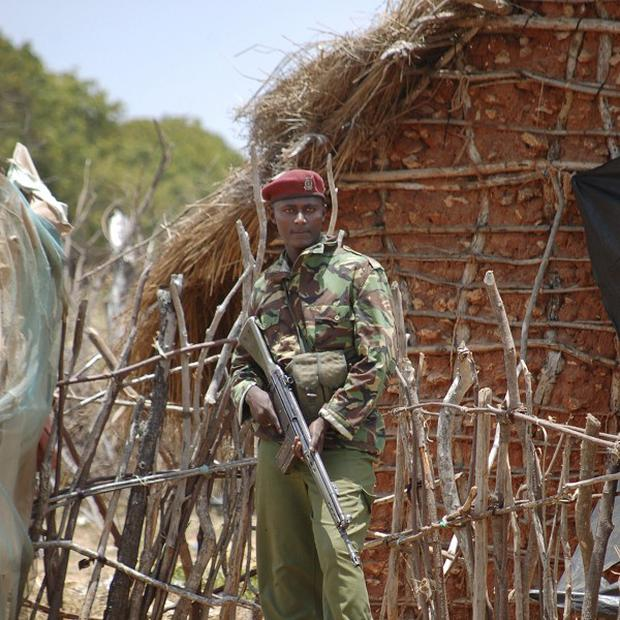 A Kenyan police officer keeps guard in a village in Kiunga, next to the border with Somalia (AP)