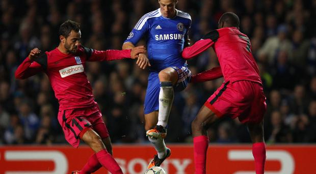 LONDON, ENGLAND - OCTOBER 19: Fernando Torres of Chelsea is challenged by Fabien Camus (L) and Khaleem Hyland of KRC Genk during the UEFA Champions League Group E match between Chelsea and KRC Genk at Stamford Bridge on October 19, 2011 in London, England. (Photo by Richard Heathcote/Getty Images)
