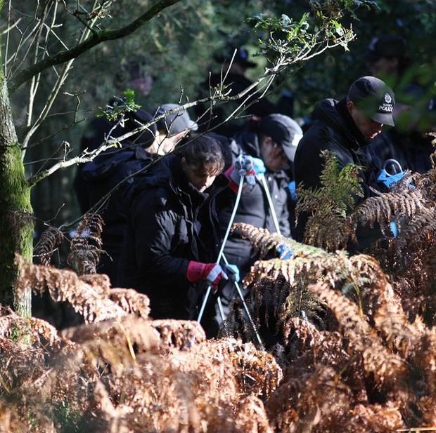 Police officers search at the scene near where the body of policewoman Heather Cooper was found
