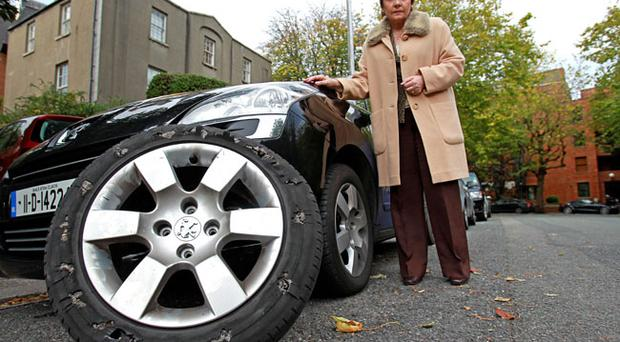 Irish Presidential candidate Dana Rosemary Scallon beside the damaged tyre