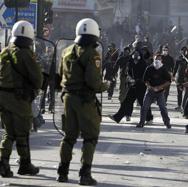 Protesters throw stones at Greek riot police during clashes in central Athens (AP)