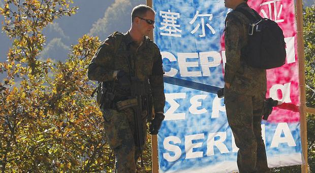German Nato soldiers next to barricades made by local Serbs on the Brnjak border between Serbia and Kosovo (AP)