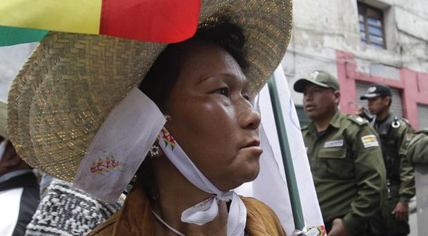 A protester is blocked by security guards from reaching the presidential palace in La Paz, Bolivia (AP)