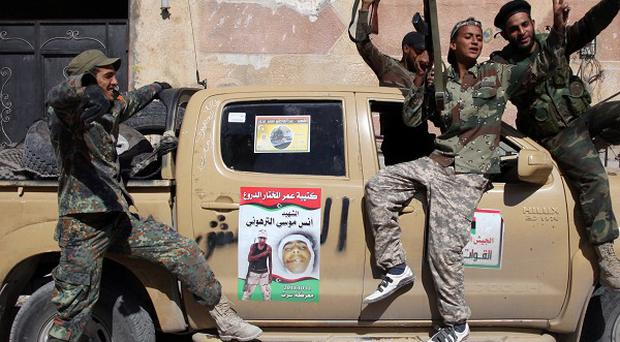 Revolutionary fighters celebrate the capture of Sirte, Libya, and the death of Muammar Gaddafi (AP)