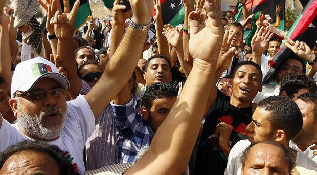 Libyans celebrate the death of Muammar Gaddafi, two months after he was driven from power (AP)
