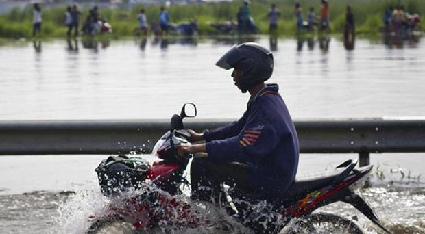 A motorcyclist on a road flooded by an overflowing canal on the outskirts of Bangkok (AP)