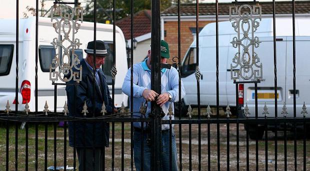 Dale Farm residents lock the gates on the legal site after removing their caravans from the illegal area