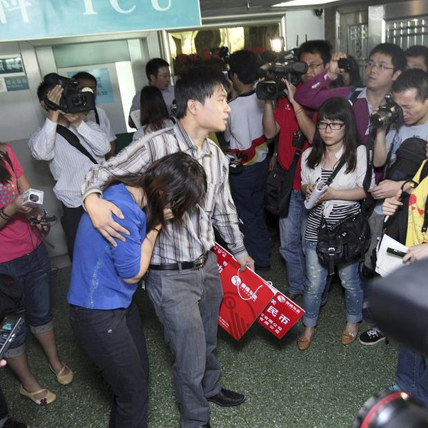 Journalists surround the parents of two-year-old Wang Yue who has died after being hit by a van (AP)