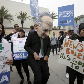 A protestor dressed as Rupert Murdoch was among dozens of people gathered outside the News Corp shareholders meeting in Los Angeles (AP)