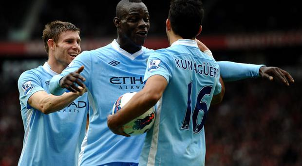 MANCHESTER, ENGLAND - OCTOBER 23: Sergio Aguero of Manchester City celebrates scoring his team's third goal with team mates James Milner (L) and Mario Balotelli during the Barclays Premier League match between Manchester United and Manchester City at Old Trafford on October 23, 2011 in Manchester, England. (Photo by Laurence Griffiths/Getty Images)