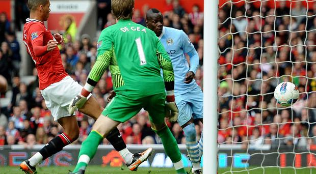 MANCHESTER, ENGLAND - OCTOBER 23: Mario Balotelli of Manchester City scores his team's second goal during the Barclays Premier League match between Manchester United and Manchester City at Old Trafford on October 23, 2011 in Manchester, England. (Photo by Laurence Griffiths/Getty Images)
