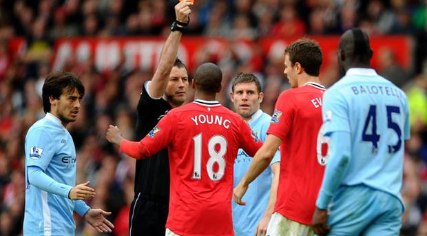 MANCHESTER, ENGLAND - OCTOBER 23: Referee Mark Clattenburg shows a red card to Jonny Evans of Manchester United during the Barclays Premier League match between Manchester United and Manchester City at Old Trafford on October 23, 2011 in Manchester, England. (Photo by Laurence Griffiths/Getty Images)