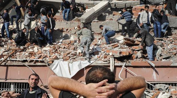 People try to save people trapped under debris in Tabanli village near the city of Van after a powerful earthquake struck eastern Turkey (AP Photos)