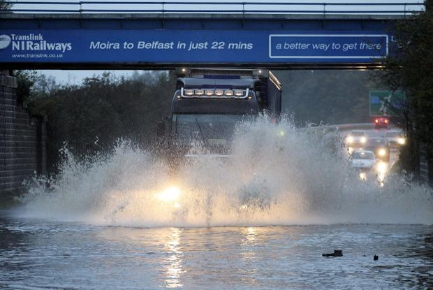 Press Eye , Belfast, Northern Ireland, - 23rd October 2011 - Picture by Kelvin Boyes / Press Eye Motorists driving through floods at Glenavy Road, Moira this evening after a day of heavy rain.