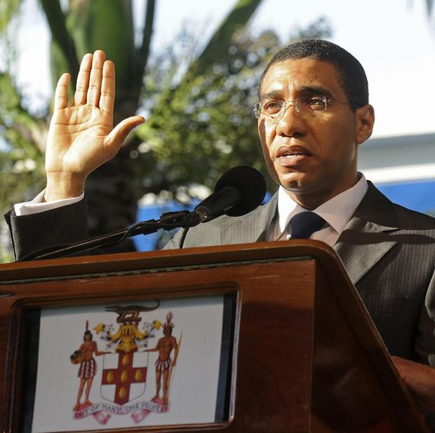 Andrew Holness takes the oath of allegiance as he beomes Jamaica's youngest prime minister (AP)