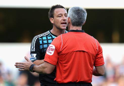 LONDON, ENGLAND - OCTOBER 23: John Terry of Chelsea argues with referee Chris Foy as he awards a penalty kick to Queens Park Rangers during the Barclays Premier League match between Queens Park Rangers and Chelsea at Loftus Road on October 23, 2011 in London, England. (Photo by Dean Mouhtaropoulos/Getty Images)