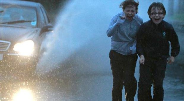 Outside the County Down Village of Mayobridge two young children make their way home in the terrible weather conditions.