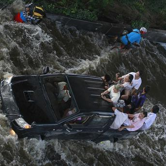Motorists make their way on a flooded street in Bangkok, Thailand (AP)