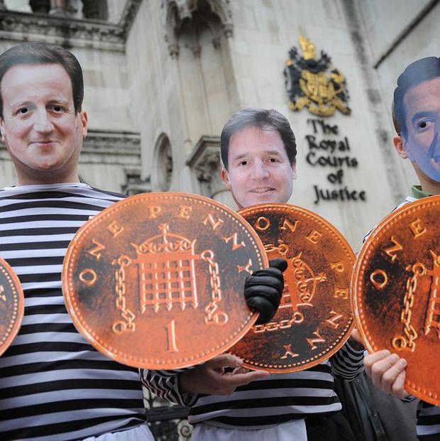 Demonstrators wearing masks of David Cameron, Nick Clegg and George Osborne protest outside the High Court in London