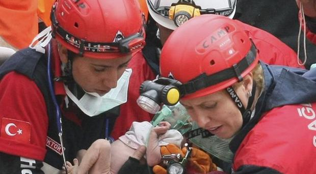 Rescuers carry Azra Karaduman, a two-week-old girl they have saved from under debris of a collapsed building in Ercis eastern Turkey(AP)