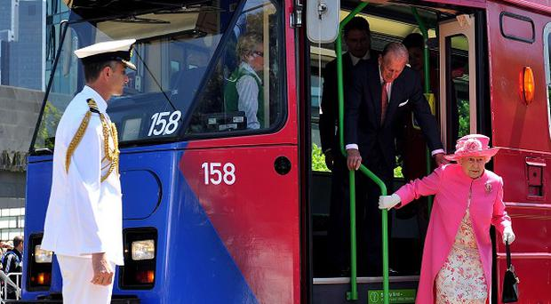 The Queen steps off an electric tram after riding through the Melbourne city centre