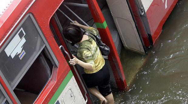 A Thai woman climbs onto the bus after wading through floodwaters in Bangkok, Thailand (AP)