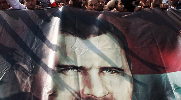 Syrian regime supporters hold up a portrait of president Bashar Assad (AP)